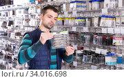 Man is considering fishing lures. Стоковое фото, фотограф Яков Филимонов / Фотобанк Лори