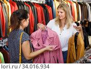 Купить «shopping assistant demonstrating female customer leather jackets in store», фото № 34016934, снято 5 сентября 2018 г. (c) Яков Филимонов / Фотобанк Лори