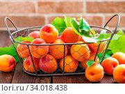 Купить «Fresh apricots with leaves in basket on wooden table», фото № 34018438, снято 4 июля 2020 г. (c) easy Fotostock / Фотобанк Лори