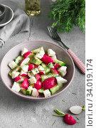 Купить «Radish, cucumber, kiwi, cheese and dill salad in a bowl on gray grunge concrete background. Seasonal Cooking, food styling.», фото № 34019174, снято 11 апреля 2019 г. (c) Nataliia Zhekova / Фотобанк Лори