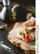 Traditional parma cured ham antipasto. Bruschetta set with Parma Ham and Parmesan Cheese. Small sandwiches with prosciutto, parmesan cheese, fresh arugula, olives and pine nuts. Стоковое фото, фотограф Nataliia Zhekova / Фотобанк Лори