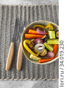 Купить «Mixed vegetable stir fry with parmesan cheese. Roasted vegetables mix on the plate with cutlery on the wicker serving mat, food above. Tender seasonal vegetables stir fry. Vegan food», фото № 34019230, снято 29 июля 2019 г. (c) Nataliia Zhekova / Фотобанк Лори