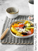 Купить «Mixed vegetable stir fry with parmesan cheese. Roasted vegetables mix on the plate with cutlery on the wicker serving mat, food above. Tender seasonal vegetables stir fry. Vegan food», фото № 34019234, снято 29 июля 2019 г. (c) Nataliia Zhekova / Фотобанк Лори