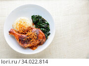 Купить «Chicken drumstick marinated with spicy chilli sauce and herbs, served with cooked rice and spinash.», фото № 34022814, снято 10 июля 2020 г. (c) easy Fotostock / Фотобанк Лори