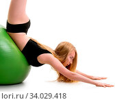 Купить «Long haired blonde in black shorts and briefs lying on her stomack on green big fitball posing in studio with her legs streching up», фото № 34029418, снято 14 июля 2020 г. (c) easy Fotostock / Фотобанк Лори