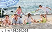 Купить «Parents and playing children on beach», фото № 34030054, снято 2 июля 2020 г. (c) Яков Филимонов / Фотобанк Лори