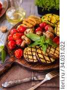 Купить «Grilled vegetables on cutting board on wooden background. Grilled vegetables (colorful bell pepper, tomatoes, onion, zucchini, eggplant) with basil», фото № 34031022, снято 20 марта 2019 г. (c) Nataliia Zhekova / Фотобанк Лори
