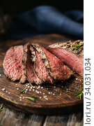 Juicy medium Beef Rib Eye steak slices on wooden board with herbs spices and salt. Стоковое фото, фотограф Nataliia Zhekova / Фотобанк Лори