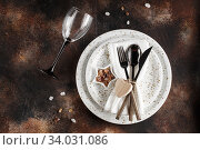 Купить «Festive table place setting. Crockery and cutlery on a dark textured background with copy space. Christmas Xmas New Year holiday background», фото № 34031086, снято 12 ноября 2019 г. (c) Nataliia Zhekova / Фотобанк Лори