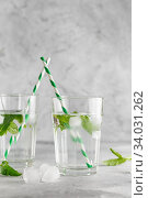 Купить «glasses of cold water with fresh mint leaves and ice cubes on grey concrete background», фото № 34031262, снято 4 июня 2019 г. (c) Nataliia Zhekova / Фотобанк Лори