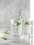 Купить «glasses of cold water with fresh mint leaves and ice cubes on grey concrete background», фото № 34031266, снято 4 июня 2019 г. (c) Nataliia Zhekova / Фотобанк Лори