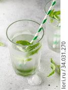 Купить «glasses of cold water with fresh mint leaves and ice cubes on grey concrete background», фото № 34031270, снято 4 июня 2019 г. (c) Nataliia Zhekova / Фотобанк Лори