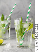 homemade lemonade with lime, mint in a glass on a gray concrete background. Healthy Fresh Mint Water with Lime and ice. Стоковое фото, фотограф Nataliia Zhekova / Фотобанк Лори