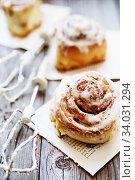 Cinnabon buns. Sinabon rolls with cream cheese and cream, chocolate and almond nuts. Стоковое фото, фотограф Nataliia Zhekova / Фотобанк Лори