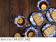 Купить «Holiday Still life. Plates with pieces of tasty cake and cups of tea with lemon on grunge wooden background. Flat lay afternoon coffee break table top shot. Relaxation time with family.», фото № 34031342, снято 8 февраля 2019 г. (c) Nataliia Zhekova / Фотобанк Лори