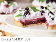 Beautiful freshly made berry meringue tart decorated with mint leaves on plate. Stunning Blackberry meringue pie still life composition. Food photography. Стоковое фото, фотограф Nataliia Zhekova / Фотобанк Лори