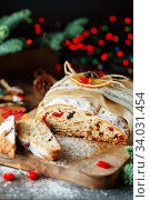 Holiday baking. Christmas cake. Stollen is fruit bread of nuts, spices, dried or candied fruit, coated with powdered sugar. It is traditional German bread eaten in the Christmas season. New year. Стоковое фото, фотограф Nataliia Zhekova / Фотобанк Лори