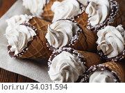 A lot of ice cream cones on wooden table. Soft ice creams or frozen custard in cones. Стоковое фото, фотограф Nataliia Zhekova / Фотобанк Лори