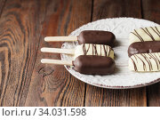 Milk chocolate popsicles on a stick. Ice cream popsicles covered with white and dark chocolate on the plate on wooden background. Space for text. Chocolate ice cream bars, nuts. Ice cream. Стоковое фото, фотограф Nataliia Zhekova / Фотобанк Лори
