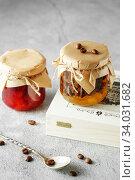 Купить «two jars of fruit homemade jam. pear marmalade with coffee beans and Jar of blood orange jam», фото № 34031682, снято 23 апреля 2019 г. (c) Nataliia Zhekova / Фотобанк Лори