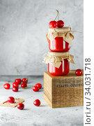 Купить «Homemade cherry jam in glass jar on the wooden box on the gray background. Two jars of cherry jam on wood with cherries in the back. Food photography. Seasonal cooking», фото № 34031718, снято 10 июня 2019 г. (c) Nataliia Zhekova / Фотобанк Лори
