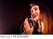 Купить «Brunette with microphone in studio on black background», фото № 34034686, снято 10 июля 2020 г. (c) easy Fotostock / Фотобанк Лори