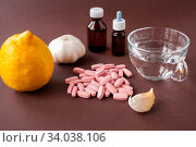 Купить «Medical still life: tablets, a mug of water, lemon, garlic and medicine in bottles on a brown background», фото № 34038106, снято 3 апреля 2020 г. (c) Катерина Белякина / Фотобанк Лори