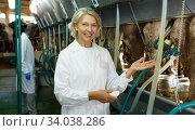 Farm milkmaid woman in bathrobe standing near automatical cow milking machines. Стоковое фото, фотограф Яков Филимонов / Фотобанк Лори
