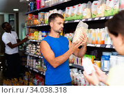 Focused muscular man looking for necessary sport nutrition products in shop, reading content label. Стоковое фото, фотограф Яков Филимонов / Фотобанк Лори