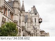 Купить «A clock projecting over the pavement on the Royal Courts of Justice building at Temple Bar, Fleet Street, London», фото № 34038602, снято 20 августа 2017 г. (c) Nataliia Zhekova / Фотобанк Лори
