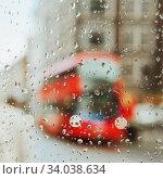 Купить «Raindrop on glass and red London bus lights background.», фото № 34038634, снято 18 августа 2017 г. (c) Nataliia Zhekova / Фотобанк Лори