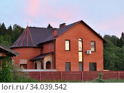 Купить «Red country house. House in suburb at summer sunset. Russia. Moscow region», фото № 34039542, снято 13 июня 2020 г. (c) Знаменский Олег / Фотобанк Лори