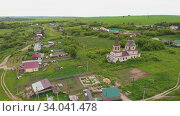 Old christian church in the middle of the field with some residential areas. Стоковое видео, видеограф Константин Шишкин / Фотобанк Лори