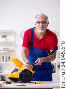 Old male contractor repairing vacuum cleaner indoors. Стоковое фото, фотограф Elnur / Фотобанк Лори
