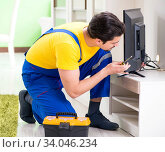 Male professional serviceman repairing tv at home. Стоковое фото, фотограф Elnur / Фотобанк Лори