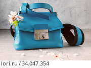fashionable turquoise Crossbody bag on the gray concrete background. Blue crossbody bag made of sheepskin and cowhide leather, a metal clasp, shoulder. Стоковое фото, фотограф Nataliia Zhekova / Фотобанк Лори