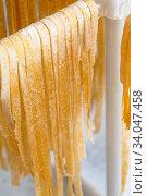 Homemade Italian tagliatelle hanging on a pasta drying rack. Fresh noodle drying on drying rack. Self-made Spaghetti Drying on a Pasta Rack. Homemade fresh egg pasta linguine hanging on rack. Стоковое фото, фотограф Nataliia Zhekova / Фотобанк Лори