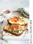Healthy eating. Toast with avocado cream and smoked salmon on the white wooden board. Smoked salmon, cream cheese and pesto toast sandwiches with radish microgreens sprouts. Стоковое фото, фотограф Nataliia Zhekova / Фотобанк Лори