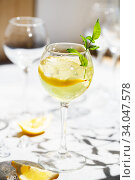 Lemonade or mojito cocktail with lemon and mint, cold refreshing drink or beverage with ice. Homemade limoncello in a glass on a thin leg. A Margarita Cocktail with a lemon slice. Стоковое фото, фотограф Nataliia Zhekova / Фотобанк Лори