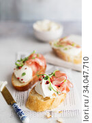 Bruschetta with prosciutto and cream cheese. Bread with smoked bacon and cream cheese. Toasted bread slice with meat and cream cheese. Стоковое фото, фотограф Nataliia Zhekova / Фотобанк Лори