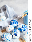 Купить «Dyed Easter eggs. Сlassic blue Easter eggs on the grey background. Blue speckled easter eggs with paint and brushes. Decorating eggs, preparing for Easter», фото № 34047722, снято 27 февраля 2020 г. (c) Nataliia Zhekova / Фотобанк Лори