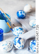 Купить «Dyed Easter eggs. Сlassic blue Easter eggs on the grey background. Blue speckled easter eggs with paint and brushes. Decorating eggs, preparing for Easter», фото № 34047726, снято 27 февраля 2020 г. (c) Nataliia Zhekova / Фотобанк Лори