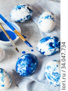 Купить «Dyed Easter eggs. Сlassic blue Easter eggs on the grey background. Blue speckled easter eggs with paint and brushes. Decorating eggs, preparing for Easter», фото № 34047734, снято 27 февраля 2020 г. (c) Nataliia Zhekova / Фотобанк Лори