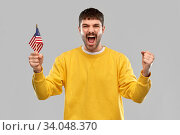 man in yellow sweatshirt with flag of america. Стоковое фото, фотограф Syda Productions / Фотобанк Лори