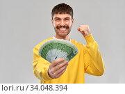 Купить «happy young man with money celebrating success», фото № 34048394, снято 22 февраля 2020 г. (c) Syda Productions / Фотобанк Лори
