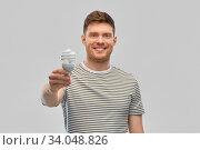 smiling young man holding lighting bulb. Стоковое фото, фотограф Syda Productions / Фотобанк Лори