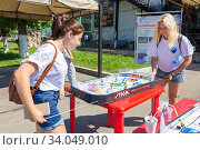 Russia, Samara, August 2016: girls play table hockey on the day of a sportsman on the embankment of the Volga River. Summer sunny day. Редакционное фото, фотограф Акиньшин Владимир / Фотобанк Лори