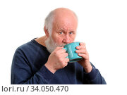 Elderly grey haired man drikns tea or coffee from blue cup isolated on white. Стоковое фото, фотограф Zoonar.com/Serghei Starus / easy Fotostock / Фотобанк Лори