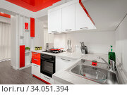 Modern spacioius red and white kitchen in apartment, premium clean design. Стоковое фото, фотограф Zoonar.com/Serghei Starus / easy Fotostock / Фотобанк Лори