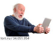 Funny shocked senior man using tablet computer, isolated on white. Стоковое фото, фотограф Zoonar.com/Serghei Starus / easy Fotostock / Фотобанк Лори